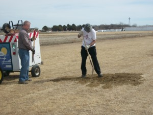 Perry Mitchell and Pat Greenwood fill a runway hole.